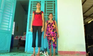 Chị Hoa với chiều cao quá khổ đứng cạnh mẹ của mình (Ảnh: Bảo Kỳ).