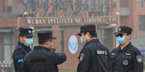 Nhân viên an ninh đứng bên ngoài Viện Virus học Vũ Hán trong chuyến thăm của nhóm chuyên gia WHO hồi tháng 2 (Ảnh: AFP).